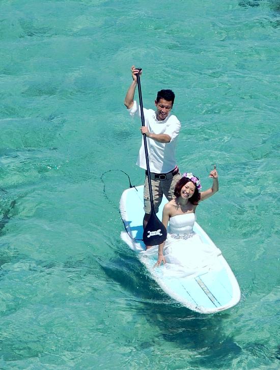 沖縄の青い海と白いウェディング衣装